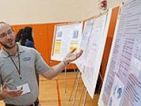 Faculty member with research poster